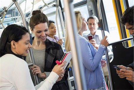 New York City park. People, men and women on a city bus. Public transport. Two women looking at a handheld digital tablet. Stock Photo - Premium Royalty-Free, Code: 6118-07354344