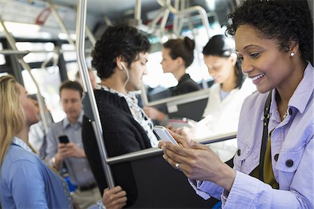 funny looking people - New York City park. People, men and women on a city bus. Public transport. Keeping in touch. A young woman checking or using her cell phone. Stock Photo - Premium Royalty-Free, Code: 6118-07354345