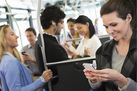 funny looking people - New York City park. People, men and women on a city bus. Public transport. Keeping in touch. A young woman checking or using her cell phone. Stock Photo - Premium Royalty-Free, Code: 6118-07354346