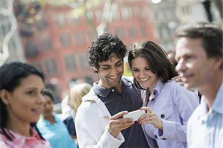 funny looking people - People outdoors in the city in spring time. New York City. A group of men and women, a couple at the centre looking at a cell phone. Stock Photo - Premium Royalty-Free, Code: 6118-07354352