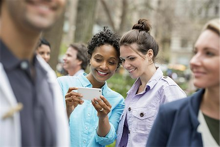 settlement - People outdoors in the city in spring time. New York City park. Two women in a group of friends, looking at a cell phone and smiling. Stock Photo - Premium Royalty-Free, Code: 6118-07354355