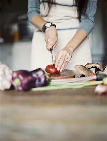 A domestic kitchen. A table top. Young woman chopping fresh vegetables with a knife. Stock Photo - Premium Royalty-Free, Code: 6118-07354390