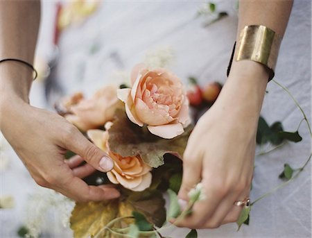 elegant - A woman arranging fresh flowers on a tabletop covered with a white cloth. Peach coloured roses. Stock Photo - Premium Royalty-Free, Code: 6118-07354391