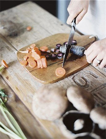 A domestic kitchen tabletop. A person chopping fresh vegetables on a chopping board with a knife. Stock Photo - Premium Royalty-Free, Code: 6118-07354392