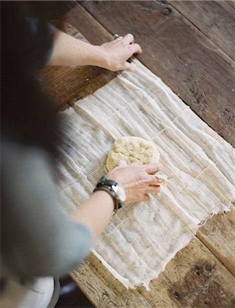 A domestic kitchen table. A view from above of a woman wrapping fresh pastry in a muslin cloth to keep it fresh. Stock Photo - Premium Royalty-Free, Code: 6118-07354395