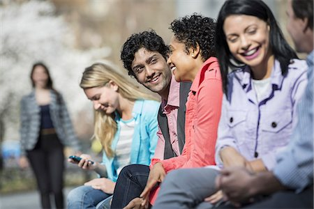 funny looking people - People outdoors in the city in spring time. Five people sitting in a row, one looking at a mobile phone. A woman approaching in the distance. Stock Photo - Premium Royalty-Free, Code: 6118-07354313