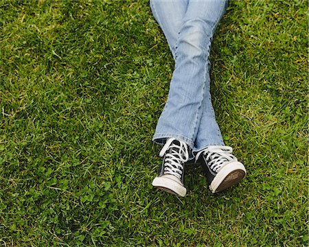 A ten year old girl lying on the grass. Cropped view of her lower legs. Wearing sneakers and faded blue jeans. Legs crossed at the ankles. Stock Photo - Premium Royalty-Free, Code: 6118-07354310