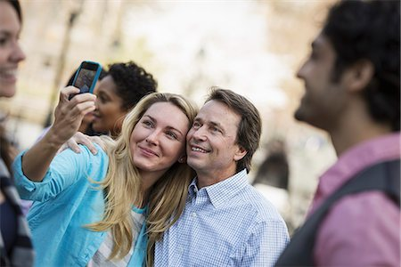 settlement - People outdoors in the city in spring time. A woman using her cell phone to take a photograph. A group of friends, men and women. Stock Photo - Premium Royalty-Free, Code: 6118-07354314