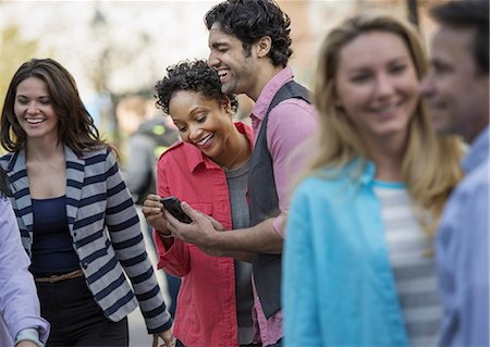 five people - People outdoors in the city in spring time. A group of men and women, two looking at a cell phone screen and laughing. Stock Photo - Premium Royalty-Free, Code: 6118-07354316