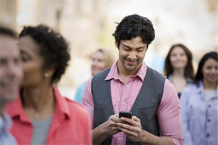 funny looking people - People outdoors in the city in spring time. A group of men and women. A man looking at his cell phone. Stock Photo - Premium Royalty-Free, Code: 6118-07354318