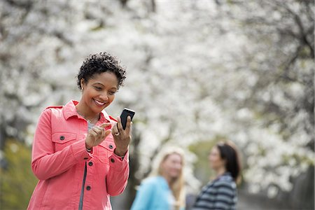 settlement - People outdoors in the city in spring time. White blossom on the trees. A young woman checking her cell phone, and laughing. Stock Photo - Premium Royalty-Free, Code: 6118-07354324