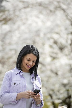 funny looking people - Outdoors in the city in spring time. New York City park. White blossom on the trees. A young woman checking her mobile phone and smiling. Stock Photo - Premium Royalty-Free, Code: 6118-07354328