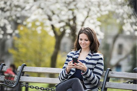 flowers - Outdoors in the city in spring time. New York City park. White blossom on the trees. A woman sitting on a bench holding her mobile phone. Stock Photo - Premium Royalty-Free, Code: 6118-07354329