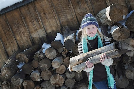 Winter scenery with snow on the ground. A girl collecting firewood from the log pile. Stock Photo - Premium Royalty-Free, Code: 6118-07354458