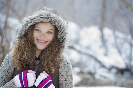 Winter scenery with snow on the ground. A young girl in a woolly hat with ski gloves on. Stock Photo - Premium Royalty-Free, Code: 6118-07354469