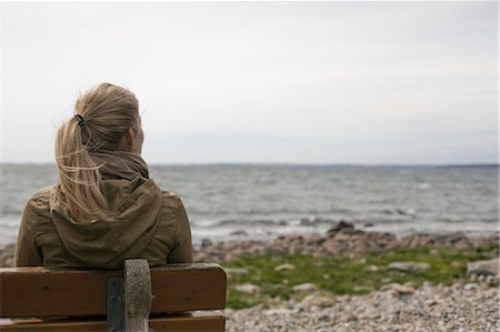 people sitting on bench - A woman with long blonde hair wearing a brown hooded coat, seated on a bench looking out to sea. Stock Photo - Premium Royalty-Free, Code: 6118-07354482
