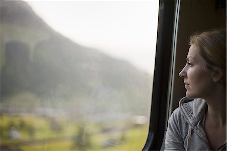 settlement - A woman sitting by a train window looking out at the landscape. Stock Photo - Premium Royalty-Free, Code: 6118-07354492