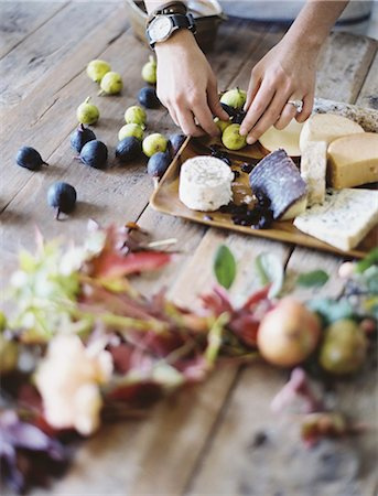 A woman at a domestic kitchen table. Arranging fresh fruit, black and green figs on a cheese board. Organic food. From farm to plate. Stock Photo - Premium Royalty-Free, Code: 6118-07354403