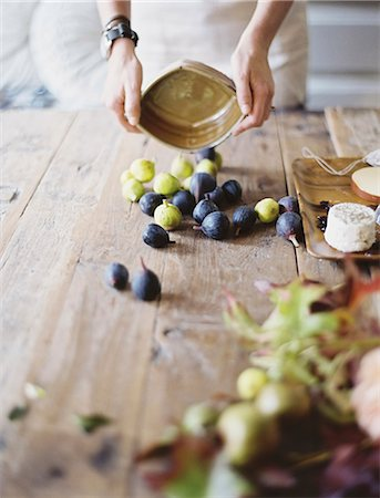 fresh - A woman at a domestic kitchen table. Arranging fresh fruit, black and green figs on a cheese board. Organic food. From farm to plate. Stock Photo - Premium Royalty-Free, Code: 6118-07354402