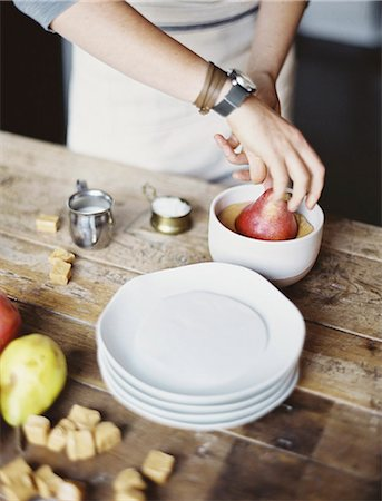 A woman in a domestic kitchen cooking. Dipping fresh organic pears into a sauce for dessert. Fresh ingredients. Brown sugar cubes. Stock Photo - Premium Royalty-Free, Code: 6118-07354407
