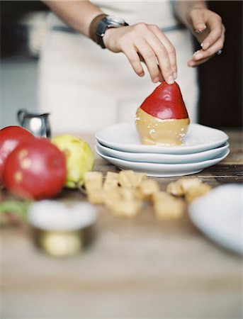 A woman in a domestic kitchen cooking. Dipping fresh organic pears into a sauce for dessert. Fresh ingredients. Brown sugar cubes Stock Photo - Premium Royalty-Free, Code: 6118-07354409