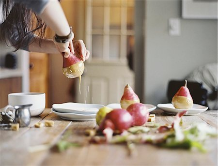 A woman in a domestic kitchen cooking. Dipping fresh organic pears into a sauce for dessert. Fresh ingredients. Brown sugar cubes Stock Photo - Premium Royalty-Free, Code: 6118-07354411