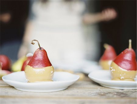 A woman in a domestic kitchen. Fresh organic pears dipped into a sauce for dessert laid out on plates. Stock Photo - Premium Royalty-Free, Code: 6118-07354412