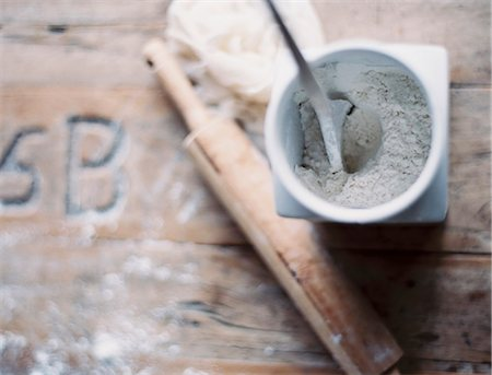 A domestic kitchen. A small group of objects. A rolling pin and jar of flour on a worn tabletop. View from above. Stock Photo - Premium Royalty-Free, Code: 6118-07354418