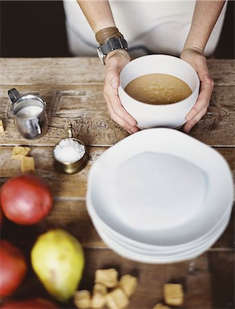 A domestic kitchen tabletop. A stack of white plates and fresh pears and a stack of sugar cubes. A bowl of  fudge sauce. Stock Photo - Premium Royalty-Free, Code: 6118-07354429
