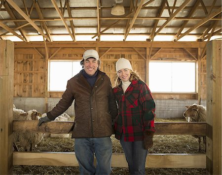 domestic sheep - An Organic Farm in Winter in Cold Spring, New York State. A farmer and a woman standing by a pen full of sheep. Stock Photo - Premium Royalty-Free, Code: 6118-07354438