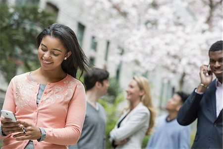 five people - City life in spring. Young people outdoors in a city park. A woman in a pink shirt checking her cell phone. Four people in the background. Stock Photo - Premium Royalty-Free, Code: 6118-07354548