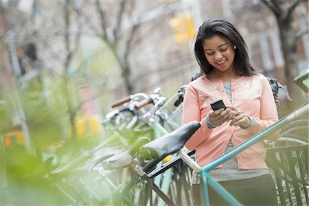 City life in spring. A young woman in a peach coloured shirt, using her smart phone. Bicycles parked in a bike rack. Stock Photo - Premium Royalty-Free, Code: 6118-07354557