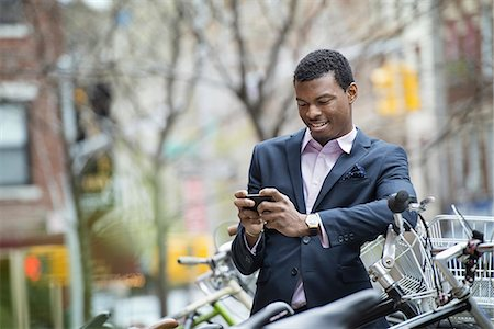 settlement - City life in spring. A young man in a blue suit, by a bicycle park. Checking his smart phone for messages. Stock Photo - Premium Royalty-Free, Code: 6118-07354559