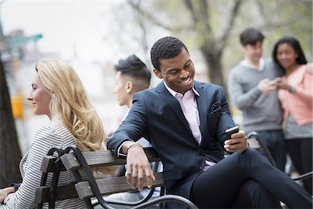 City life in spring. Young people outdoors in a city park. A group of men and women gathered around a park bench. Two checking a smart phone for messages. Stock Photo - Premium Royalty-Free, Code: 6118-07354564