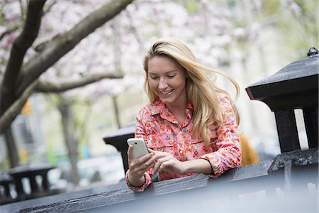 City life in spring. A young woman with long blonde hair sitting in a city park, looking at her smart phone. Stock Photo - Premium Royalty-Free, Code: 6118-07354571
