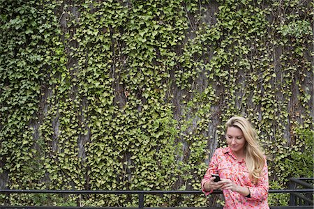 City life in spring. City park with a wall covered in climbing plants and ivy.  A young blonde haired woman checking her smart phone. Stock Photo - Premium Royalty-Free, Code: 6118-07354587