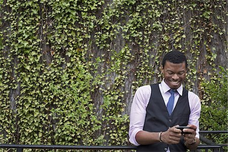 City life in spring. City park with a wall covered in climbing plants and ivy.  A young man in a waistcoat, shirt and tie checking his phone. Stock Photo - Premium Royalty-Free, Code: 6118-07354589