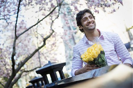 rose patterns - City life. A young man in the park in spring, holding a bunch of yellow roses. Stock Photo - Premium Royalty-Free, Code: 6118-07354500