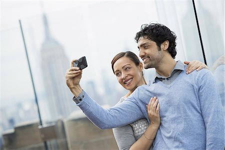 settlement - New York City. An observation deck overlooking the Empire State Building. A young couple taking photographs with a mobile phone. Stock Photo - Premium Royalty-Free, Code: 6118-07354509