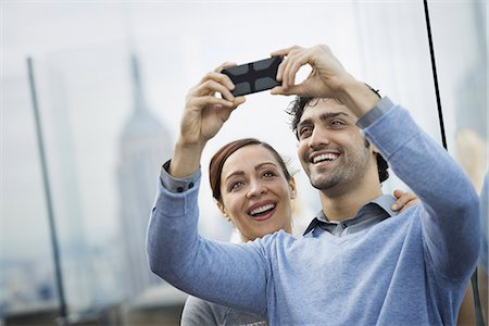 settlement - New York City. An observation deck overlooking the Empire State Building. A young couple taking photographs with a mobile phone. Stock Photo - Premium Royalty-Free, Code: 6118-07354510