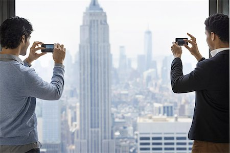 settlement - Urban lifestyle. Two young men using their phones to take images of the city from an observation platform overlooking the Empire State Building. Stock Photo - Premium Royalty-Free, Code: 6118-07354523