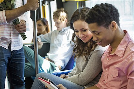 Urban Lifestyle. A group of people, men and women on a city bus, in New York city. A couple side by side looking at a digital tablet. Stock Photo - Premium Royalty-Free, Code: 6118-07354528