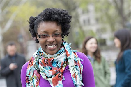 A group of people in a city park. A young woman smiling, wearing a purple shirt and floral scarf. Stock Photo - Premium Royalty-Free, Code: 6118-07354641