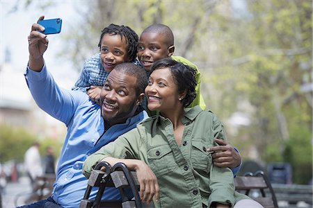 A New York city park in the spring. A family, parents and two boys taking a photograph with a smart phone. Stock Photo - Premium Royalty-Free, Code: 6118-07354685