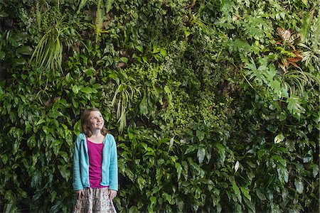 Outdoors in the city in spring. An urban lifestyle. A young girl standing in front of a wall covered with ferns and climbing plants. Stock Photo - Premium Royalty-Free, Code: 6118-07354753