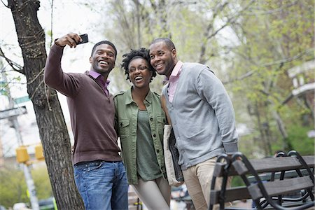 Outdoors in the city in spring. An urban lifestyle. Three people posing together and one taking a photograph of them with a smart phone. Stock Photo - Premium Royalty-Free, Code: 6118-07354737