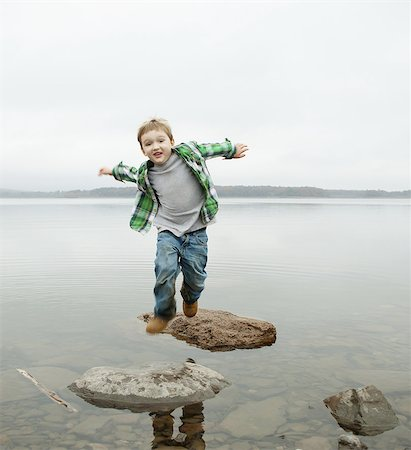 A day out at Ashokan lake. A boy jumping across stepping stones. Stock Photo - Premium Royalty-Free, Code: 6118-07440277