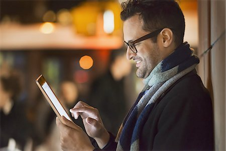 A man in a city at night, looking at a computer tablet. Stock Photo - Premium Royalty-Free, Code: 6118-07440408