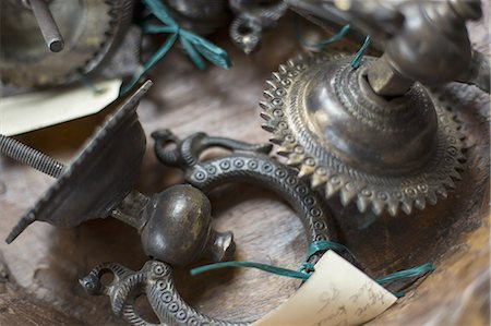 An antique store with a display of objects and furniture from the past. Chased metal decorated objects, door knocker and light fitting. Stock Photo - Premium Royalty-Free, Code: 6118-07440552