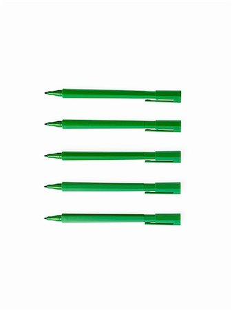 five - Office supplies. Green coloured pens, felt nibs and pen top cases, arranged in a row. Stock Photo - Premium Royalty-Free, Code: 6118-07440743